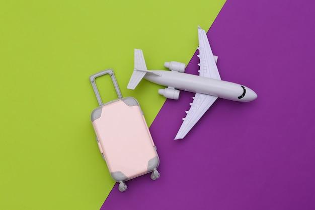 Trajeto plano de viagens aéreas. mini mala de viagem de plástico e avião de ar em fundo roxo verde. vista do topo.