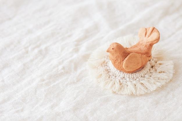 Trança artesanal de pássaro de barro e macramê e fios de algodão. imagem boa para banners e propaganda de macramê e artesanato. copie o espaço
