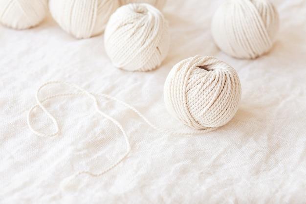 Trança de macramé artesanal e fios de algodão em fundo branco.