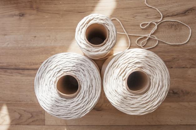 Trança de macramê artesanal e fios de algodão na mesa de madeira rústica. carretel de fio de algodão tricô hobby em uma placa de madeira. passatempo feminino. top vew