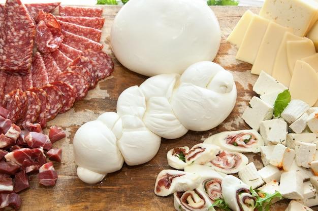 Trança em forma de mussarela na tábua com salame e queijo.