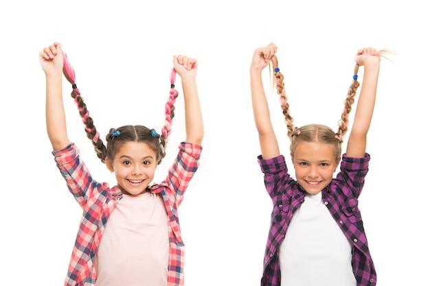 Tranças longas de meninas. tendência da moda. cutie elegante. infância feliz. mantenha o cabelo trançado. irmãs com longos cabelos trançados. salão de cabeleireiro. se divertindo. espírito rebelde. estilo de escola de penteados.