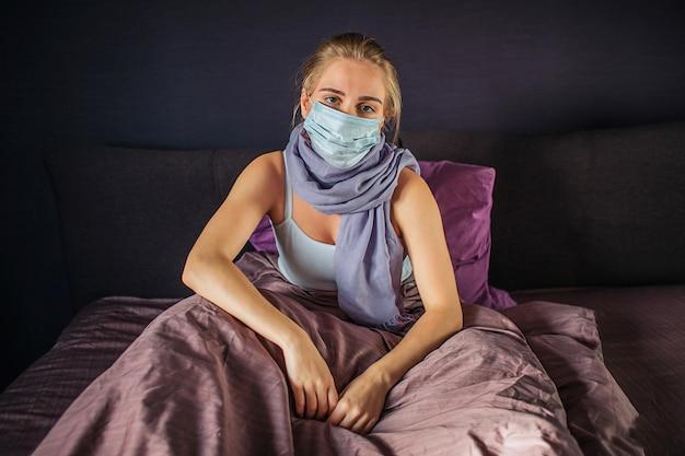 Tranquila e grave jovem infectada senta-se na cama e olha para a câmera. ela está coberta com um cobertor. jovem mulher tem um pouco de descanso.