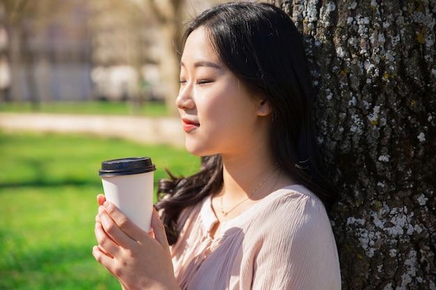 Tranquila garota tranquila desfrutando de café para viagem no parque da cidade