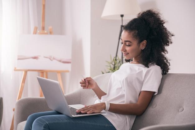 Transação de dinheiro. mulher simpática e encantada digitando os dados do cartão de crédito enquanto faz um pagamento online