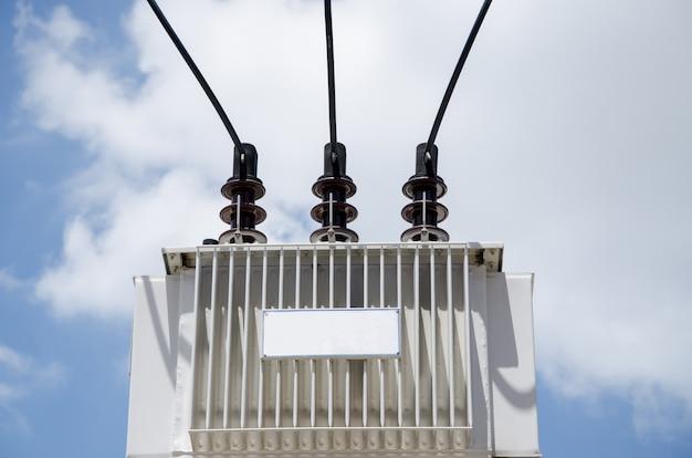 Transformador definido no alto com fundo de céu azul.
