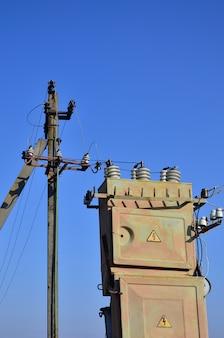 Transformador elétrico velho e obsoleto na perspectiva de um céu azul sem nuvens.