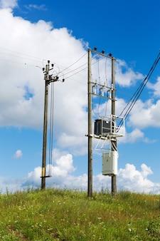 Transformadores de uma coluna elétrica com cabos de linhas de energia contra o céu azul brilhante. transformador com os postes de eletricidade no campo.
