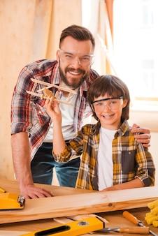 Transformando suas visões em realidade. jovem carpinteiro alegre abraçando seu filho enquanto se inclina na mesa de madeira com diversas ferramentas de trabalho colocadas sobre ela
