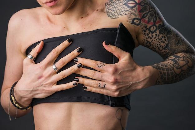 Transgênero moleca não binária usando sutiã de encadernação para problema de identidade estética de seios pequenos