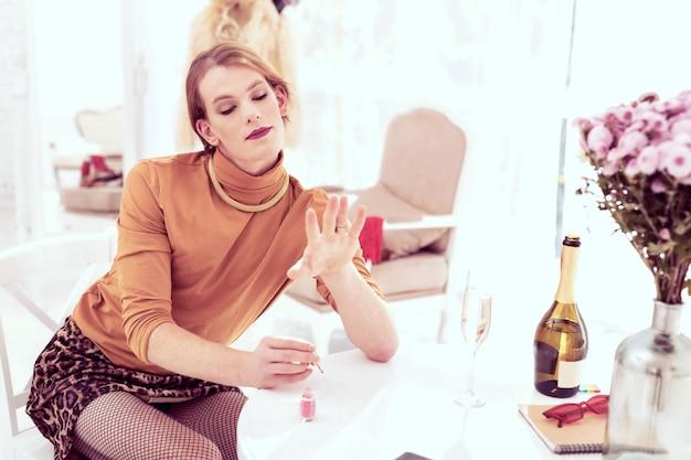 Transgênero soprando. jovem transexual elegante satisfeita com o seu trabalho enquanto olha para as unhas pintadas
