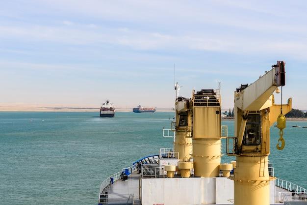 Trânsito do canal de suez. vista do navio de carga. trabalho no mar. remessa comercial.