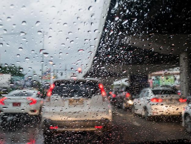 Trânsito em dia chuvoso com vista da estrada pela janela do carro com gotas de chuva