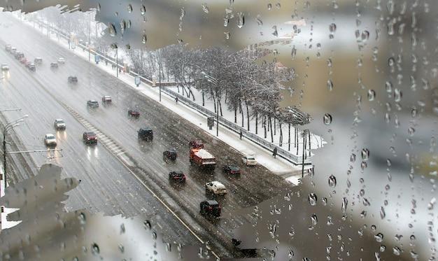 Trânsito em dia de forte neve com vista da estrada dentro da janela da casa embaçada com gotas de água