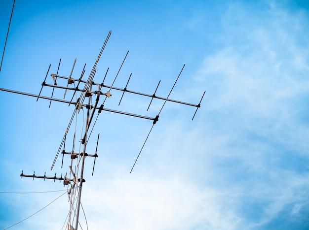 Transmissão de sinal velha da antena de televisão em azul-céu. comunicação de tv de tecnologia antiga.