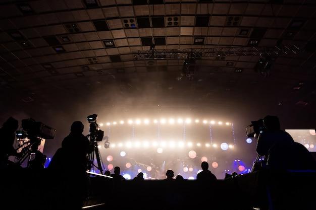 Transmissão de televisão por um cinegrafista durante um concerto. a câmera com o operador está na plataforma alta.