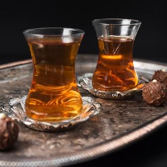 Transparentes xícaras de chá na bandeja de prata