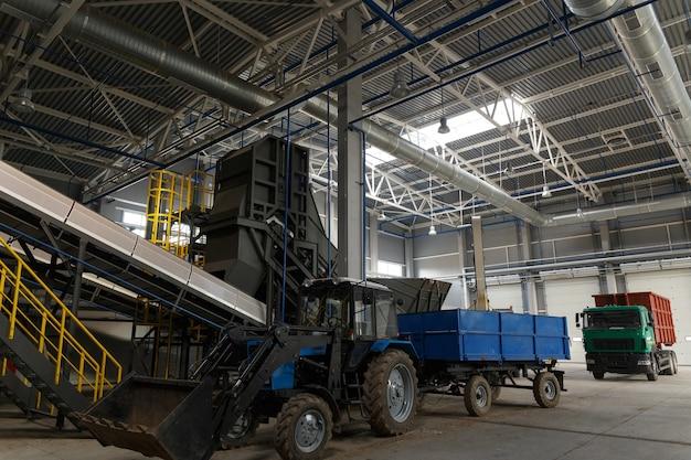 Transportador central da estação de triagem de resíduos. reciclagem e armazenamento de resíduos para posterior disposição. um trator para carregar resíduos. um caminhão para a retirada de resíduos reciclados.
