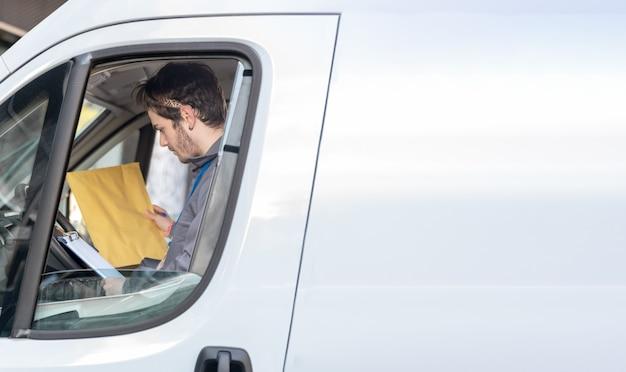 Transportadora com uniforme no assento do motorista olhando os pacotes para entregar os pedidos