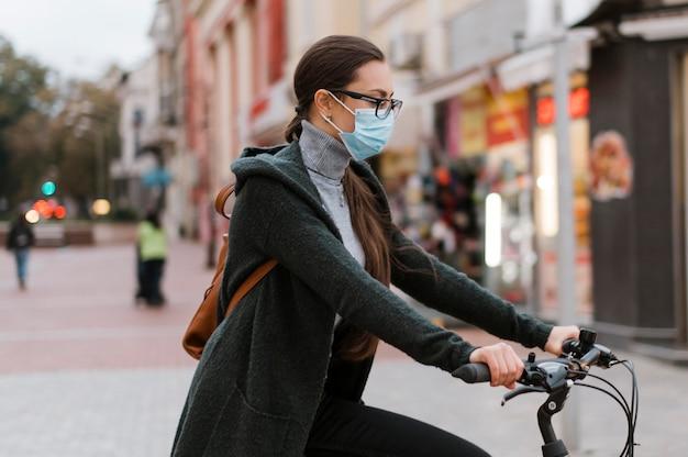 Transporte alternativo de bicicleta e mulher usando máscara