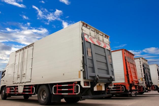 Transporte de caminhões estacionado com um céu azul.