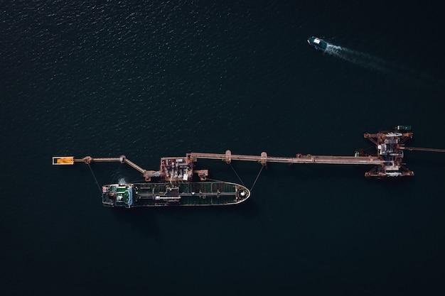 Transporte de carga e descarga de tanque de óleo na vista aérea do mar