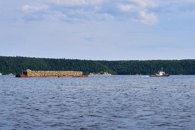 Transporte de madeira ao longo do rio usando uma barcaça rebocada por um rebocador