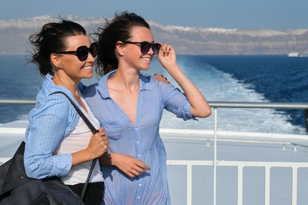 Transporte de passageiros, mãe e filha adolescente no convés da balsa. feliz viagem em família, fundo, céu marinho da ilha grega de santorini, hora de ouro