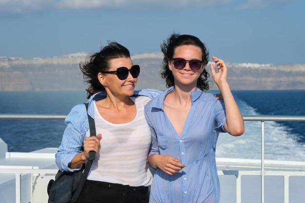 Transporte de passageiros, mãe e filha adolescente no convés da balsa. feliz viagem em família, fundo do céu da ilha grega de santorini, hora dourada