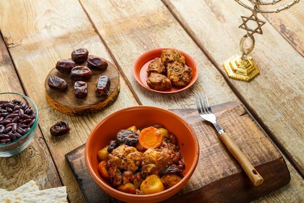 Transporte de prato judaico com carne em um prato sobre uma mesa de madeira ao lado de pão ázimo. garfo e ingredientes. foto horizontal