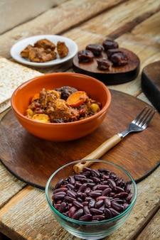 Transporte de prato judaico com carne na mesa em um prato perto dos ingredientes. foto vertical