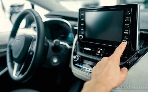 Transporte e conceito de veículo - homem usando o sistema estéreo de áudio do carro