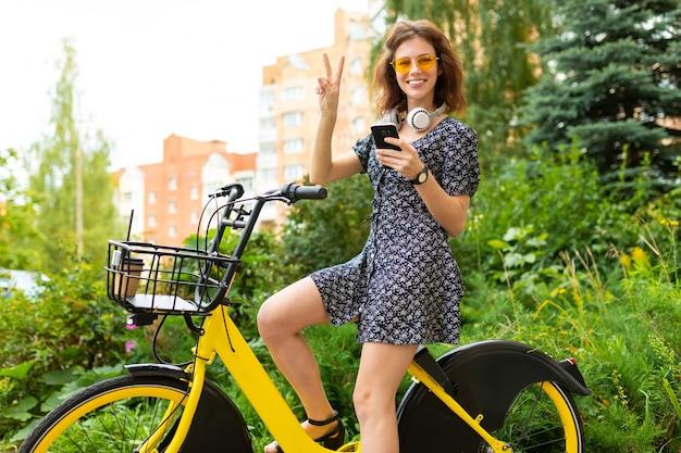 Transporte ecológico. linda garota europeia anda de bicicleta alugada em um parque da cidade e abre o caminho ao telefone.