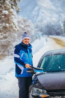 Transporte, inverno, clima, homens e conceito de veículo homem removendo a neve do pára-brisa do carro marrom com escova