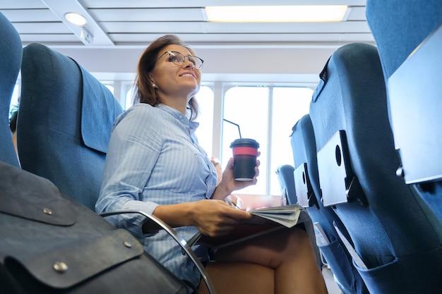Transporte marítimo de passageiros, mulher sentada na cabine de uma confortável balsa marítima, descansando, lendo uma revista, bebendo café, viagens marítimas, turismo