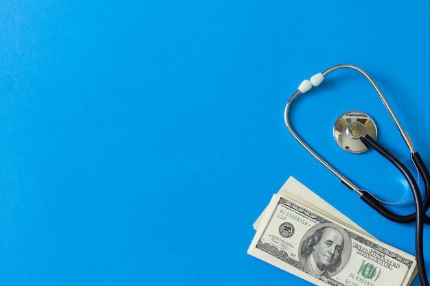 Tratamento caro. estetoscópio e dólares em fundo azul