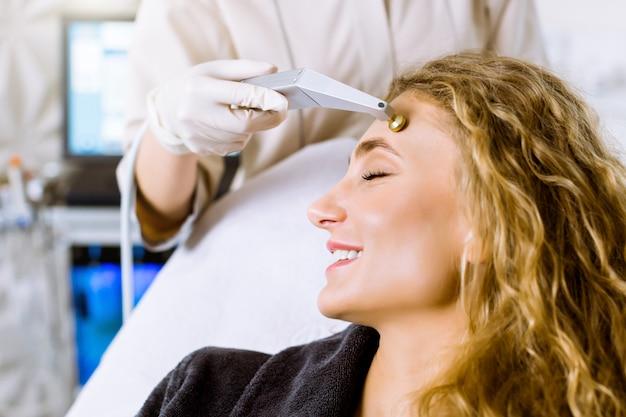 Tratamento clínico de microdermoabrasão, procedimento facial estético, anti acne e cosméticos para hiperpigmentação. mão de cosmetologista, fazendo a microdermoabrasão para a jovem mulher loira sorridente.