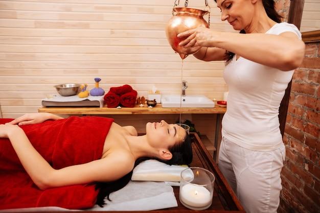Tratamento com óleo. mulher experiente e diligente carregando reservatório de metal e derramando óleo medicinal no rosto