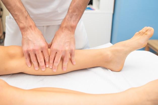Tratamento da perna de um atleta por um fisioterapeuta