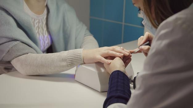 Tratamento das unhas no salão. o mestre aplica laca gel nas unhas de uma jovem.
