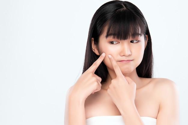 Tratamento de acne. mulher com acne. jovem mulher apertando a espinha, removendo a espinha do rosto. conceito de cuidados de pele de mulher. mulher de cuidados de beleza de pele de espinha de mancha de acne local pressionando no rosto de problema de pele.