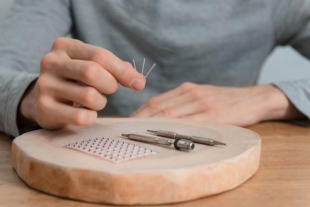 Tratamento de acupuntura nas mãos do homem, agulhas.