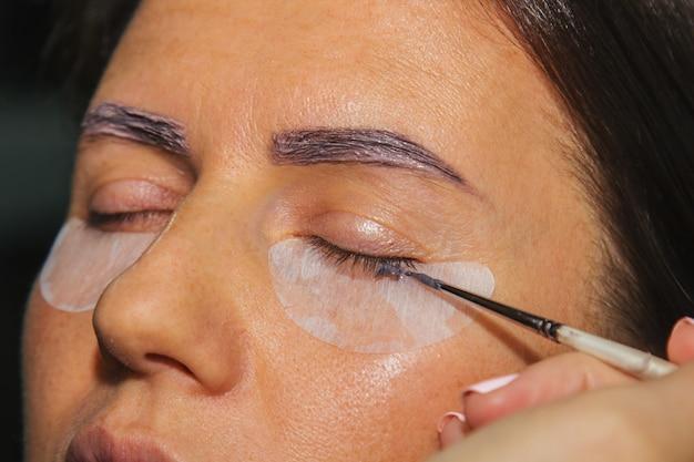 Tratamento de beleza. closeup rosto de mulher com tinta nas pestanas. pestanas de laminação. vista lateral.