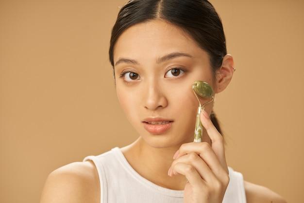 Tratamento de beleza facial bela jovem olhando para a câmera enquanto recebe massagem facial usando