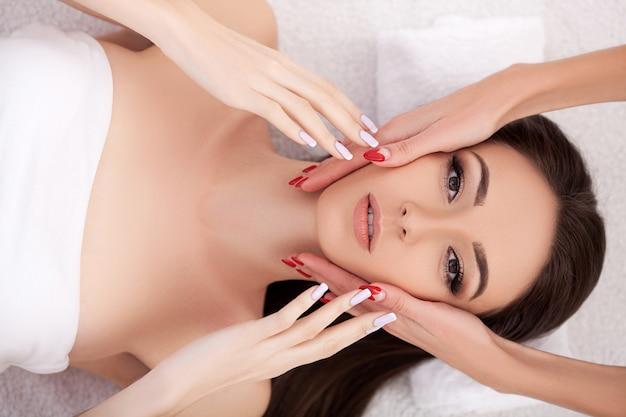 Tratamento de beleza facial. closeup de mulher bonita, recebendo tratamento de beleza, massagem nas mãos no salão spa dia. massauer massageando o rosto feminino com óleo de aromaterapia. cuidados com a pele e o corpo.