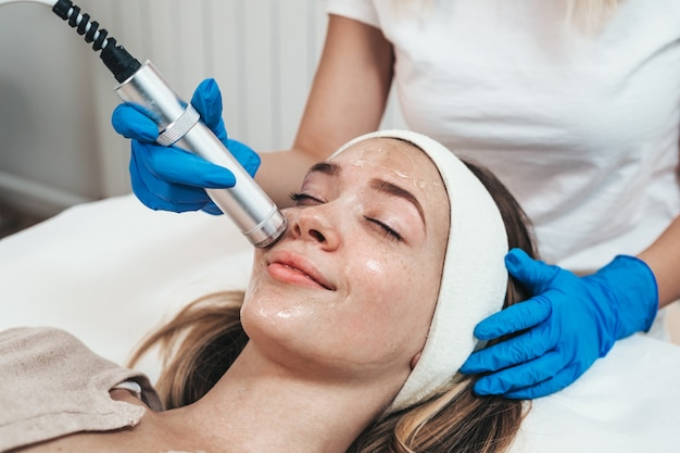 Tratamento de beleza facial de mulher jovem e bonita com oxigênio no salão de beleza cosmético.