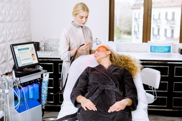 Tratamento de beleza facial na clínica moderna de cometologia. mulher encaracolada loira e bonita, tendo terapia de luz led vermelha