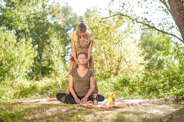 Tratamento de beleza. massagista fazendo massagem no corpo da mulher na floresta.