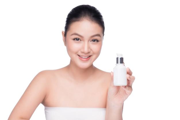 Tratamento de beleza. mulher asiática segurando frasco de soro hidratante