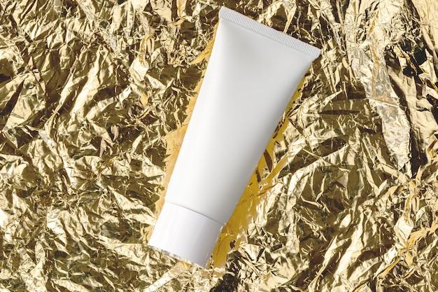Tratamento de beleza para a pele e loção cosmética creme frasco de óleo embalagem produto plano lay. tubo branco para hidratante, limpador facial, xampu em textura de metal amassada dourada vista superior